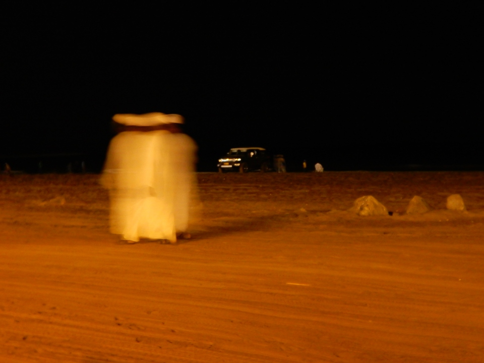 A blur of men on the beach.